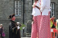 Town Crier looking up to stilt people